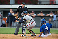 Danville Braves catcher Carlos Martinez (8) waits for the throw as Meibrys Viloria (4) of the Burlington Royals slides across home plate at Burlington Athletic Park on July 12, 2015 in Burlington, North Carolina.  The Royals defeated the Braves 9-3. (Brian Westerholt/Four Seam Images)