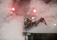 Pictured: A fireman extinguishes a fire in a refuse bin outside the Toumba Stadium in Thessaloniki, Greece. Sunday 25 February 2018<br /> Re: Sunday's Greek Super League derby between PAOK Thessaloniki and Olympiakos was called off after Olympiakos' manager Oscar Garcia was struck in the face by an object believed to be a till machine paper roll, thrown by a spectator minutes before kick-off.<br /> Garcia left Toumba Stadium for a local hospital to seek treatment for a bloodied lip.<br /> The incident prompted the Olympiakos team to leave the pitch in protest before riots erupted outside the ground.<br /> Angry PAOK fans leaving the stadium then clashed with police who used tear gas to quell the violence.