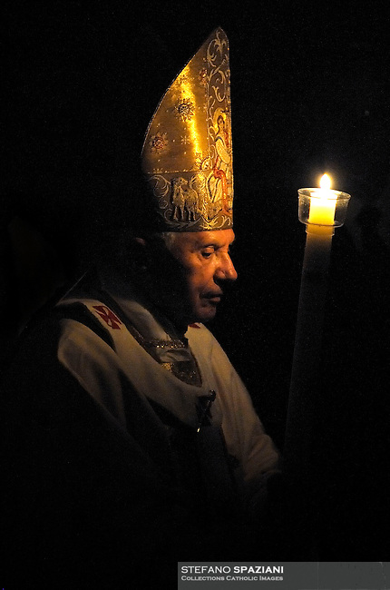Pope Benedict XVI holds a candle during the Easter vigil mass in Saint Peter's Basilica, in the Vatican, late  April 23, 2011
