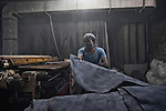 A labour covers up his mouth and nostrils with a cloth while working in a tannery in Jajmau area, Kanpur. Exposure to the harmful chemicals used in the tannery causes skin diseases, respiratory diseases, gastro-intestinal ailments etc. Researches have shown presence of elevated amount of chromium in the blood and urine of the workers. Kanpur, Uttar Pradesh, India. Arindam Mukherjee