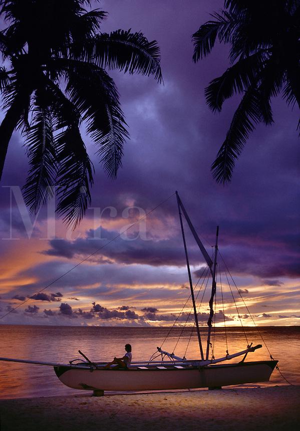 Girl Sitting on Outrigger Canoe Sunset at Bora Bora Lagoon Bora Bora French Polynesia.