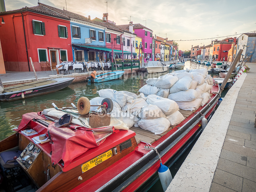 Cargo boat. The colorful village of Burano, Italy.