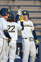 Michigan Wolverines first baseman Jimmy Kerr (15) celebrates with teammate Jordan Brewer (22) after scoring against the San Jose State Spartans on March 27, 2019 in Game 2 of the NCAA baseball doubleheader at Ray Fisher Stadium in Ann Arbor, Michigan. Michigan defeated San Jose State 3-0. (Andrew Woolley/Four Seam Images)
