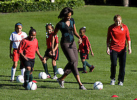 Michelle Obama participates in a drill under the watchful eye of USWMNT defender Rachel Buehler during a Lets Move! soccer clinic held on the South Lawn of the White House.  Let's Move! was started by Mrs. Obama as a way to promote a healthier lifestyle in children across the country..