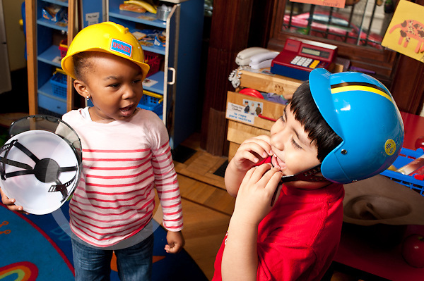 Education Preschool 3-4 year olds boy and girl playing with dressup helmets