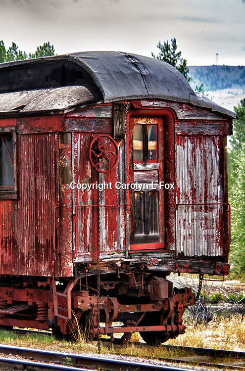 An old antique train sits on railroad tracks.