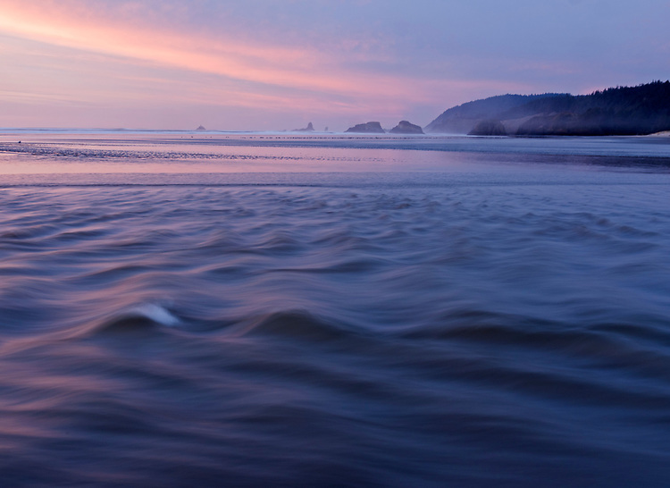 Waves roll into Cannon Beach, with Ecola State Park in the background, during a colorful sunset on the northern coast of Oregon, USA