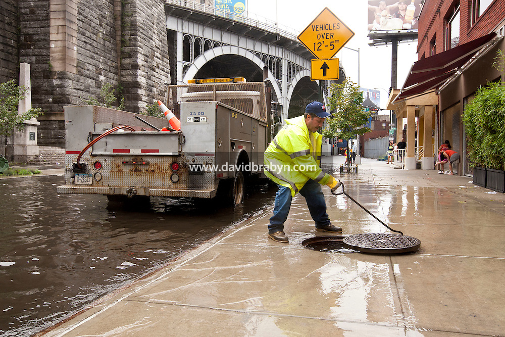 A New York City Department of Environmental Protection employee checks a drain in a rain water flooded section of 12th Avenue in Hamilton Heights, New York City, NY, USA shortly after tropical storm Irene passed over the city, 28 August 2011.
