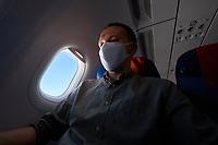 Passenger wearing mask in airplane