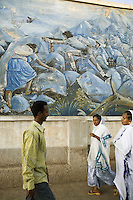 Eritrea. Maekel province. Asmara. Passers-by ( a man and two women with white cotton loincloths on their heads)walk in front of a wall painting which shows a taste of history on the 30 years liberation war against ethiopian war planes. The eritrean fighters with their weapons are displayed in fresco, as symbols of the freedom for the eritrean state and its people. © 2006 Didier Ruef