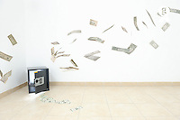 Banknotes flying out a safe in empty room (Licence this image exclusively with Getty: http://www.gettyimages.com/detail/103627278 )