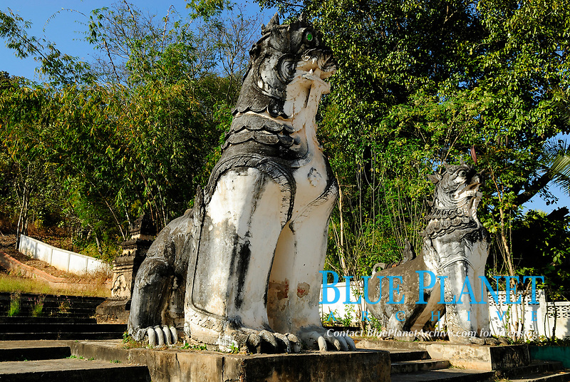 Stone lion statue in front of Wat Phra Non temple in Mae Hong Son city, Thailand, Southeast Asia. Wat Phra Non, the 'Monastery of the Reclining Buddha' stands at the eastern foot of the hill where Wat Phra That Doi Kong Mu is located. The 12 meter Buddha image was built of bricks and concrete by a ruler of Mae Hong Son in 1875. The main architectural point of interest is the Burmese-style mondop with its fine multi-tiered metal roof.
