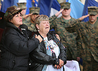 X.memorial.1.1207.jl.jpg/photo Jamie Scott Lytle/Sandra Aceves, of Chula Vista, looks to the American Flag flying at half mast during the playing of TAPS, as she holds Sheila Cobb of Florida during the 5th. Marine Regiment and Regimental Combat Team 5 Memorial Dedication held on Camp Pendleton Friday. Aceves and Cobb's sons, Corpsman Fernando Mendez and PFC Chris Cobb died together in April 2004 while serving in Iraq.