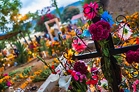 A decorated black cross is seen at a flower-adorned grave during the Day of the Dead celebrations in Oaxaca, Mexico, 1 November 2019. Day of the Dead (Día de Muertos), a religious holiday combining the death veneration rituals of Pre-Hispanic cultures with the Catholic practice, is widely celebrated throughout all of Mexico. Based on the belief that the souls of the departed may come back to this world on that day, people gather together while either praying or joyfully eating, drinking, and playing music, to remember friends or family members who have died and to support their souls on the spiritual journey.