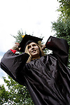 A young woman graduating with a diploma certificate adusting her cap