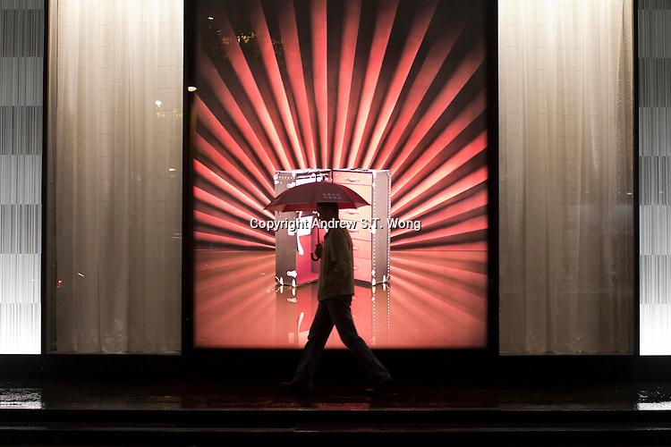 A man walks past a French boutique in a rainy Nanjing, Jiangsu province, China, November 2012.