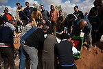 Family and friends move a body into a fresh grave during a mass funeral for 20 people, killed during fighting between opposition rebels and loyalist forces of Col. Muammar Qaddafi, in Benghazi, Libya, March 20, 2011. The main hospital in Benghazi reported around 50 dead fighters and civilians the previous day and at least 35 on Sunday.