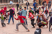 Bhaktapur, Nepal.  Masked Figure Chasing a Student in Durbar Square.