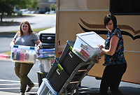Michelle Kitchens (from left) and Meredith Young, director of Harding University, carry personal care items, Monday, September 13, 2021 at Harding University in Rogers. Members of the Harding student body paid for and collected over $10,000 worth of personal care items for incoming refugees. The items will go to Canopy NWA who will disperse the items. Check out nwaonline.com/210914Daily/ for today's photo gallery. <br /> (NWA Democrat-Gazette/Charlie Kaijo)
