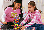11 year old girl playing block stacking game w. friend, age 11