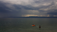 WEATHER PICTURE<br /> Two boys play with a rubber ring as dark clouds and rain are seen over the bay of south Evia minutes before a monsoon type storm hits Nireas beach near Aliveri on the island of Evia, Greece. The country has been experiencing recent heatwaves. Thursday 27 July 2017