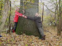 Kinder, Junge und Mädchen, Geschwister, Kind umfassen den dicken Stamm einer alten Eiche, Quercus robur, Oak