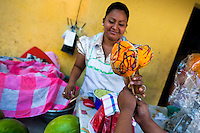 """A Salvadoran woman sells mango with chocolate on a stick during the Flower & Palm Festival in Panchimalco, El Salvador, 8 May 2011. On the first Sunday of May, the small town of Panchimalco, lying close to San Salvador, celebrates its two patron saints with a spectacular festivity, known as """"Fiesta de las Flores y Palmas"""". The origin of this event comes from pre-Columbian Maya culture and used to commemorate the start of the rainy season. Women strip the palm branches and skewer flower blooms on them to create large colorful decoration. In the afternoon procession, lead by a male dance group performing a religious dance-drama inspired by the Spanish Reconquest, large altars adorned with flowers are slowly carried by women, dressed in typical costumes, through the steep streets of the town."""