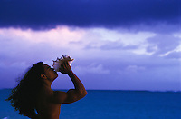 Young Hawaiian man blowing conch shell at sunrise
