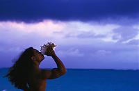Young Hawaiian man blowing conch shell at sunrise