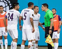 Fiorentina players discuss Arsenal's goal with the assistant referee