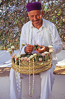 Tunisia, Sidi Bou Said.  Jasmine Seller Bahri Mabrook, in Traditional Tunisian Men's Clothing, including a burgundy-colored chechia, the traditional Tunisian hat.