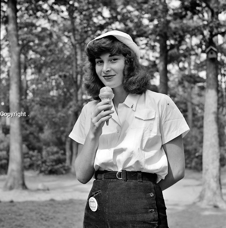 A student eating an ice cream cone at the National music camp in Interlochen, Michigan where 300 or more young musicians study symphonic music for 8 weeks each summer. August 1942.<br /> <br /> Photo by Arthur S. Siegel.