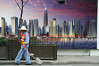 A street sweeper walks past a billboard showing an artist's depiction of the Pudong skyline at dusk in Shanghai, China..