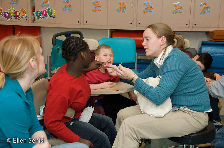 MR / Albany, NY.Langan School at Center for Disability Services .Ungraded private school which serves individuals with multiple disabilities.Teacher holds up alphabet letters for child to identify while teaching assistant and another child watch. She is sitting in a rifton advancement chair. Girl: 10, African-American, cerebral palsy, expressive and receptive language delays; Boy: 9, cerebral palsy, non verbal with expressive and receptive language delays.MR: AH-cfds.© Ellen B. Senisi