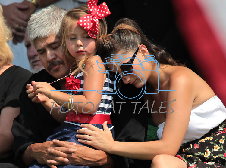 Family members of Colorado shooting victim Jonathan Blunk comfort his daughter Hailey, 4, during a graveside service in Reno, Nev. on Friday morning, Aug. 3, 2012. Hailey's grandfather Hector Ramos and her aunt Kristel Lu were among the estimated 500 people who attended the service. (AP Photo/Cathleen Allison)