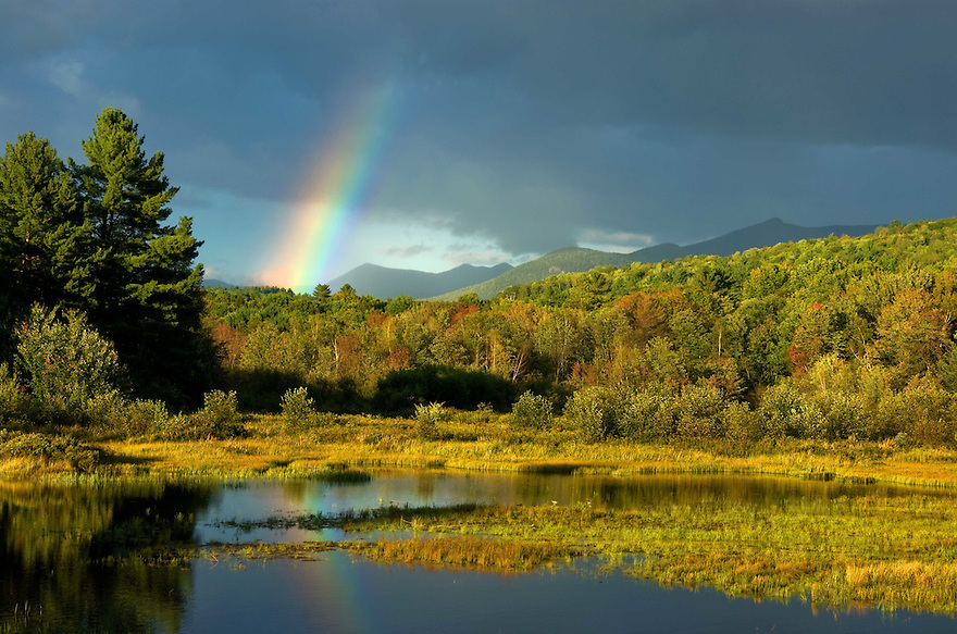 A shaft of color pours from the sky in front of Campton Pond and mountains beyond.