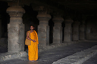 Buddhist Monk inside one of the Ellora Caves Aurangabad, India.The famous Ellora caves are located in the lap of the Chamadari hills. These historical caves are regarded as world heritage and are situated 18 miles northwest of Aurangabad.  .A wonderful example of cave temple architecture, the world heritage Ellora caves own elaborate facades and intricately carved interiors. These carved structures on the inner walls of the caves reflect the three faiths of Hinduism, Buddhism and Jainism. These exotic caves were carved during 350 AD to 700 AD period. .Ellora caves are hewn out of basaltic rock of the Deccan trap, and are datable from circa 5th century A.D. to 11th century A.D. In all 34 caves were excavated here out of which Cave 1 to 12 are Buddhist, 13 to 29 are Brahmanical and 30 to 34 are Jaina. Cave10 in AjantaCavescontains theoldest Indian paintingsof historical period, made around the 1st century BC.<br /> <br /> ThecavesatAjantadate from the 2nd century B.C.E. to 650 C.E andwerecut into the mountainside in two distinct phases. Discovered by chance in 1819 by British soldiers on a hunt, theAjanta Caveshave become an icon of ancient Indian art, and have influenced subsequent artists and styles.<br /> <br /> Thesepaintingsbeautifully depict various events in the life of Lord Buddha. All the caves are divided into two categories namely the Chaityas or the shrines and the Viharas or the monasteries. Chaityas were used to worship Lord Buddha while the Viharas were used by the Buddhist monks for their meditation