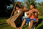 Father and sons playing the violin, harp, and mandolin outside their thatched hut in a traditional Mayan village in Southern Belize