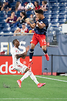 FOXBOROUGH, MA - MAY 22: Brandon Bye #15 of New England Revolution heads a ball near the sideline during a game between New York Red Bulls and New England Revolution at Gillette Stadium on May 22, 2021 in Foxborough, Massachusetts.