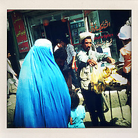 A burqa clad woman and a child buy bananas from a street stall.