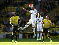 Ashley Williams of Swansea head the ball under pressure from Steven Berghuis of Watford and Troy Deeney of Watford   during the Barclays Premier League match Watford and Swansea   played at Vicarage Road Stadium , Watford