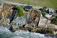 aerial photograph of a house ready to fall into the Pacific Ocean because of erosion on the Pacific Coast along Highway One in Sonoma County, California, the remains of a collapsed house on the left