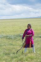 Mongolia, Gobi Gurvan Saikhan National Park, Gobi Desert, archery at small Naadam festival at Three Camel Lodge. Badmaa, girl archer.