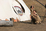 A young Native American Indian girl hugging her brother near their tipi