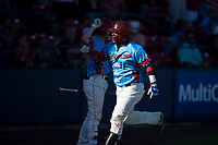 Spokane Indians catcher Isaias Quiroz (11) is congratulated by Jax Biggers (1) after hitting a home run during a Northwest League game against the Vancouver Canadians at Avista Stadium on September 2, 2018 in Spokane, Washington. The Spokane Indians defeated the Vancouver Canadians by a score of 3-1. (Zachary Lucy/Four Seam Images)