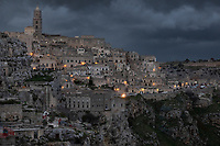 """Italy. Basilicata Region. Matera. On a stormy sunset afternoon, a view on the historical centre. Known as la Città Sotterranea (""""the Underground City""""), Matera is one of the oldest continuously inhabited cities in the world, having been inhabited since the 10th millennium BC. Its historical centre """"Sassi"""", along with the Park of the Rupestrian Churches, was awarded World Heritage Site status by UNESCO since 1993. The Sassi di Matera are two districts (Sasso Caveoso and Sasso Barisano), well-known for their ancient cave dwellings.The Sassi originate from a prehistoric troglodyte settlement and are suspected to be among the first human settlements in Italy. There is evidence that people were living here as early as the year 7000 BC.The Sassi are houses dug into the calcarenite rock itself, which is characteristic of Basilicata, locally called """"tufo"""" although it is not volcanic tuff or tufa. The streets in some parts of the Sassi often run on top of other houses. The ancient town grew up on one slope of the ravine created by a river that is now a small stream. The ravine is known locally as """"la Gravina"""". In the 1950s, the government of Italy forcefully relocated most of the population of the Sassi to areas of the developing modern city. Until the late 1980s this was considered an area of poverty, since many of these houses were, and in some cases still are, uninhabitable. The current local administration, however, has become more tourism-oriented, and it has promoted the regeneration of the Sassi with the aid of the European Union, the government, UNESCO. Today there are many thriving businesses, pubs, restaurants and hotels. On 17th October 2014, Matera was declared Italian host of European Capital of Culture for 2019. Basilicata is a region in Southern Italy. 8.12.18  © 2018 Didier Ruef"""
