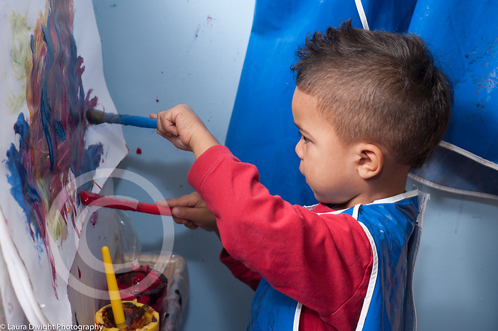 Education preschool 3-4 year olds art activity boy painting at easel using two brushes, one in each hand