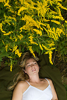 Blonde woman laying on grass surrounded by goldenrod