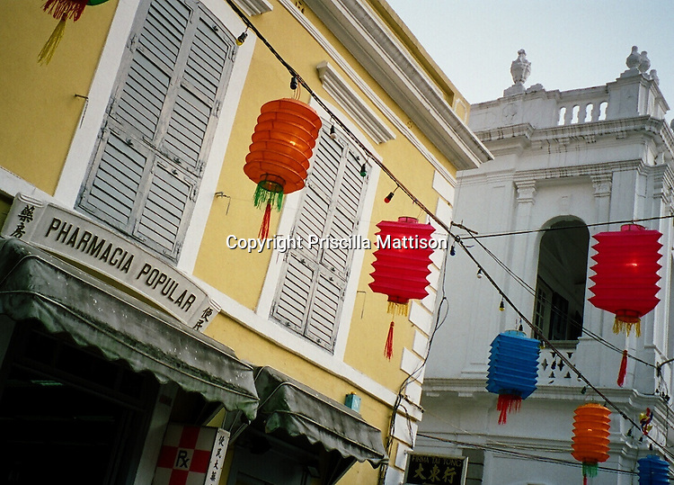 Chinese lanterns hang in front of two colonial buildings in Macau.