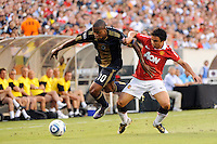 Danny Mwanga (10) of the Philadelphia Union flies over the leg of Fabio (20) of Manchester United. Manchester United (EPL) defeated the Philadelphia Union (MLS) 1-0 during an international friendly at Lincoln Financial Field in Philadelphia, PA, on July 21, 2010.
